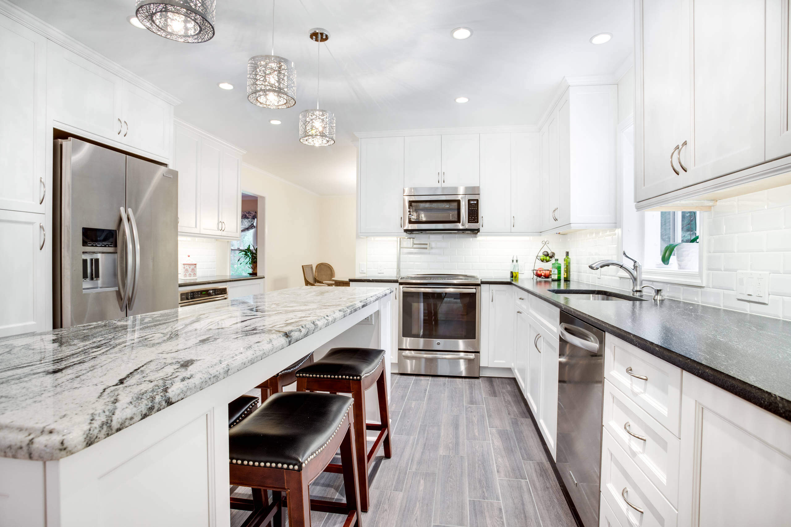 Example of a large transitional u-shaped kitchen design in DC Metro with an undermount sink, recessed-panel cabinets, white cabinets, granite countertops, white backsplash, subway tile backsplash, stainless steel appliances and an island