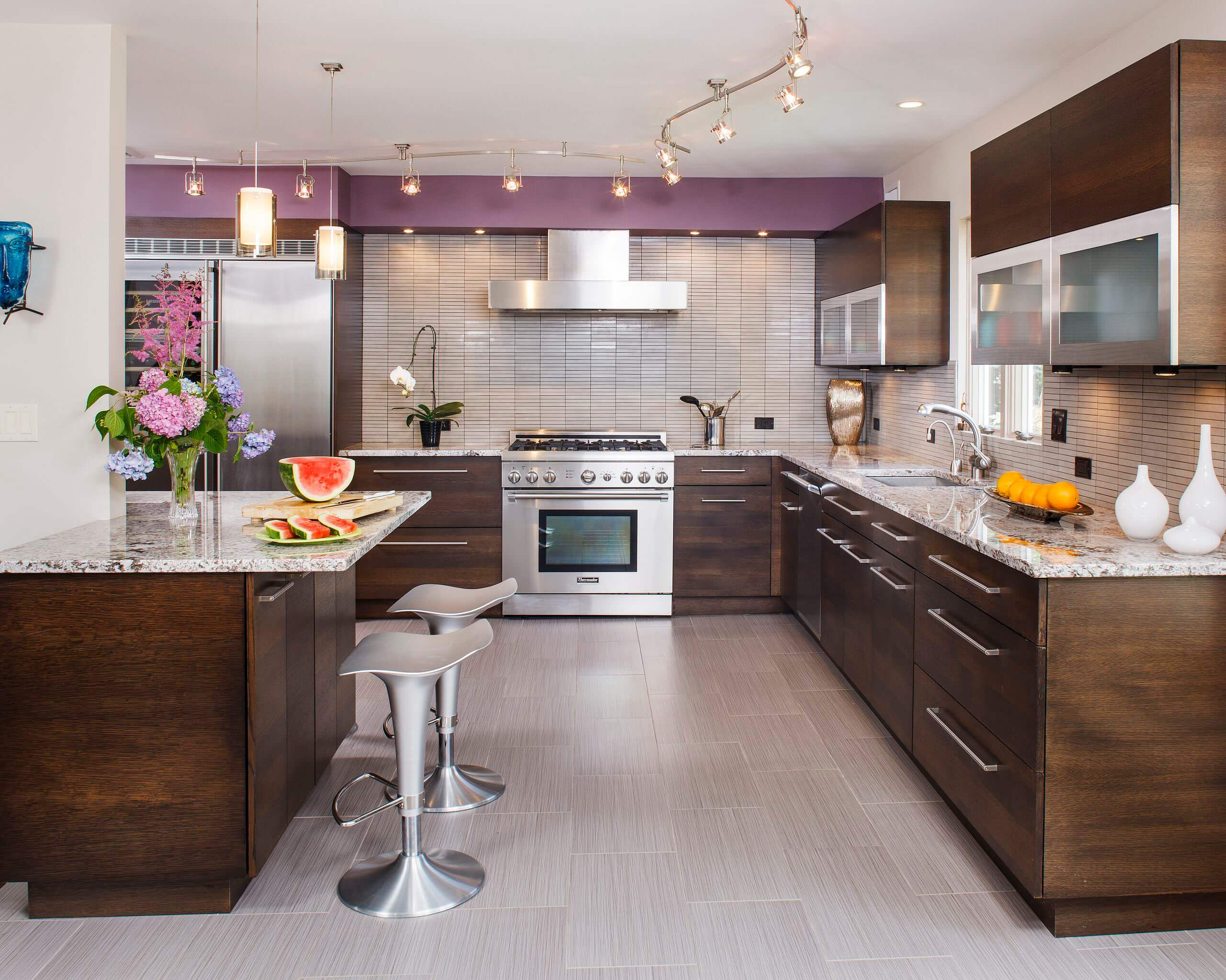 Kitchen - contemporary kitchen idea in New York with flat-panel cabinets, dark wood cabinets, beige backsplash and stainless steel appliances