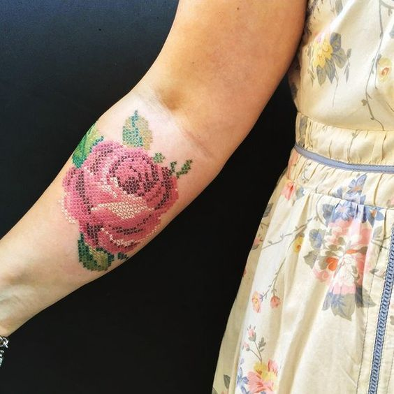 Girl showing her tattooed forearm with a large red rose with cross stitch embroidery effect
