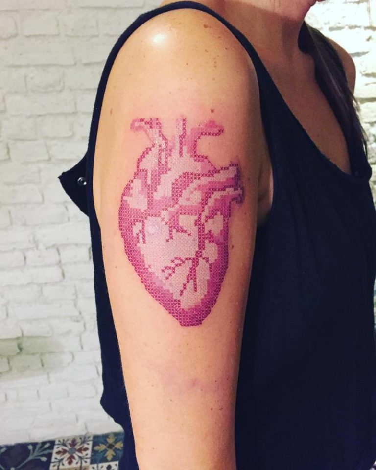 Thin person showing heart tattoo with cross stitch embroidery effect on his right arm