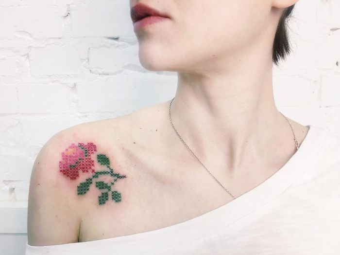 Woman recharged on a white wall, looking sideways, with bare shoulder to show her rose tattoo with cross-stitch embroidery effect