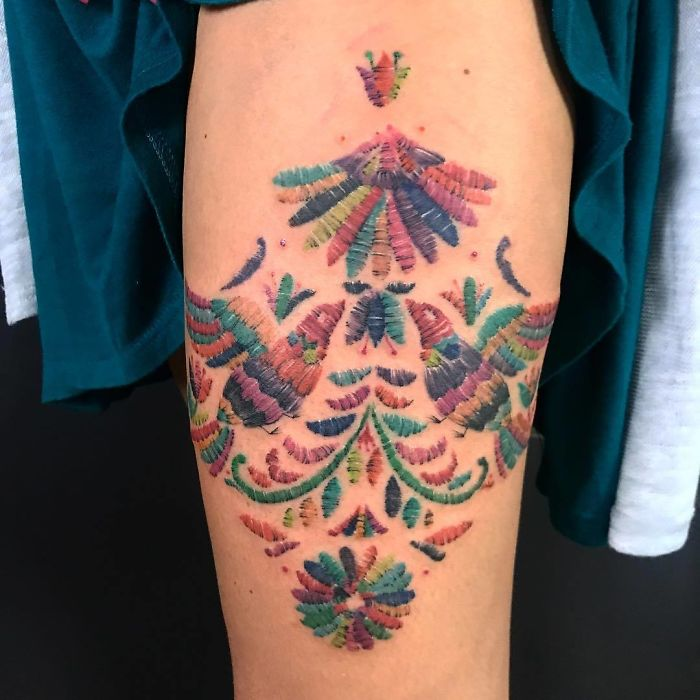 Tattoo of colorful birds looking at the sun with embroidered effect