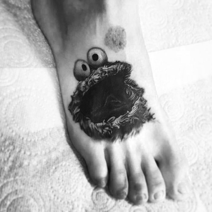 Boy with a monster tattoo eats cookies on his foot