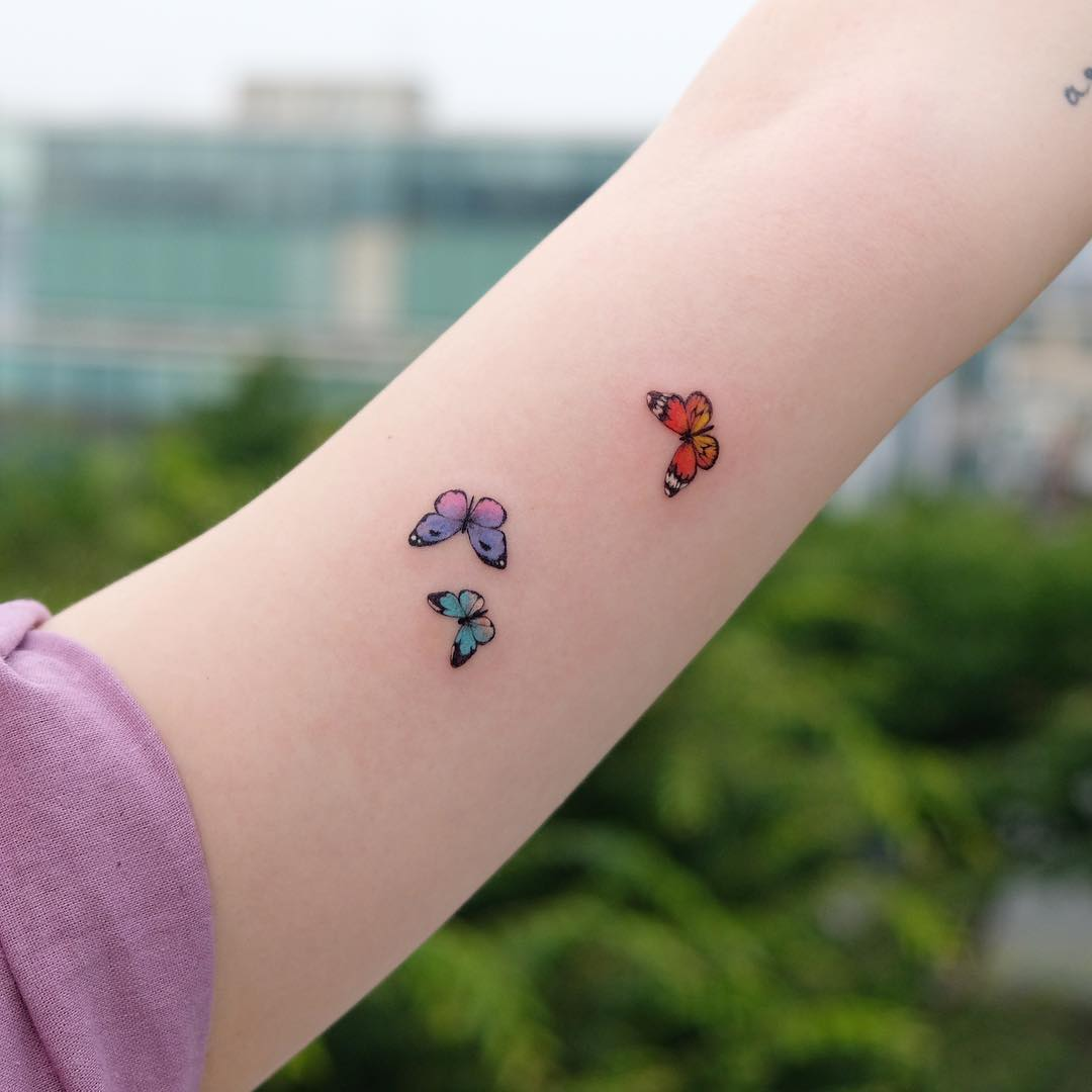 Girl with a tattoo of three butterflies of different colors