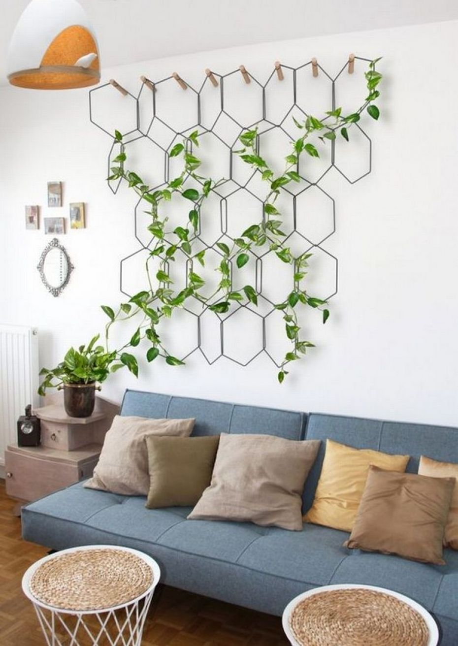 Living room decoration with a climbing plant installed in a rhombic metal structure on a blue armchair with brown cushions