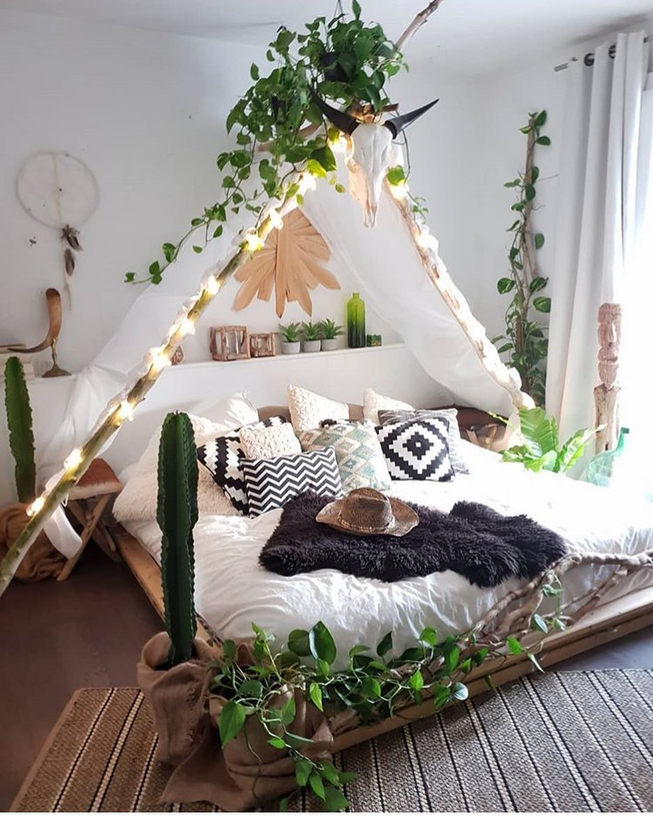 Room decorated with a tepee in the center of the bed and on it there are green plants that help to decorate the blank space