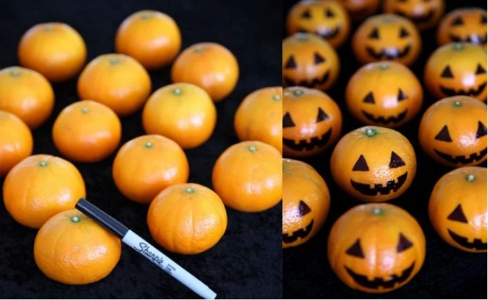 Tangerines decorated as pumpkins.