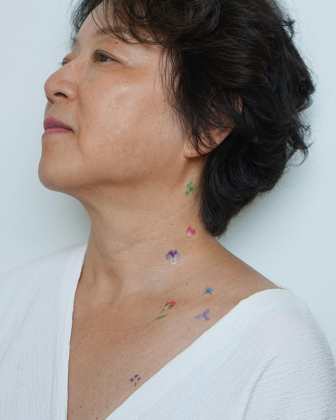 Girl with a tattoo of a few flowers on her neck