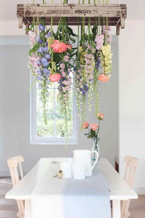 Dining room of a house in neutral colors, decorated with a cascade of flowers that hang from the ceiling to the table