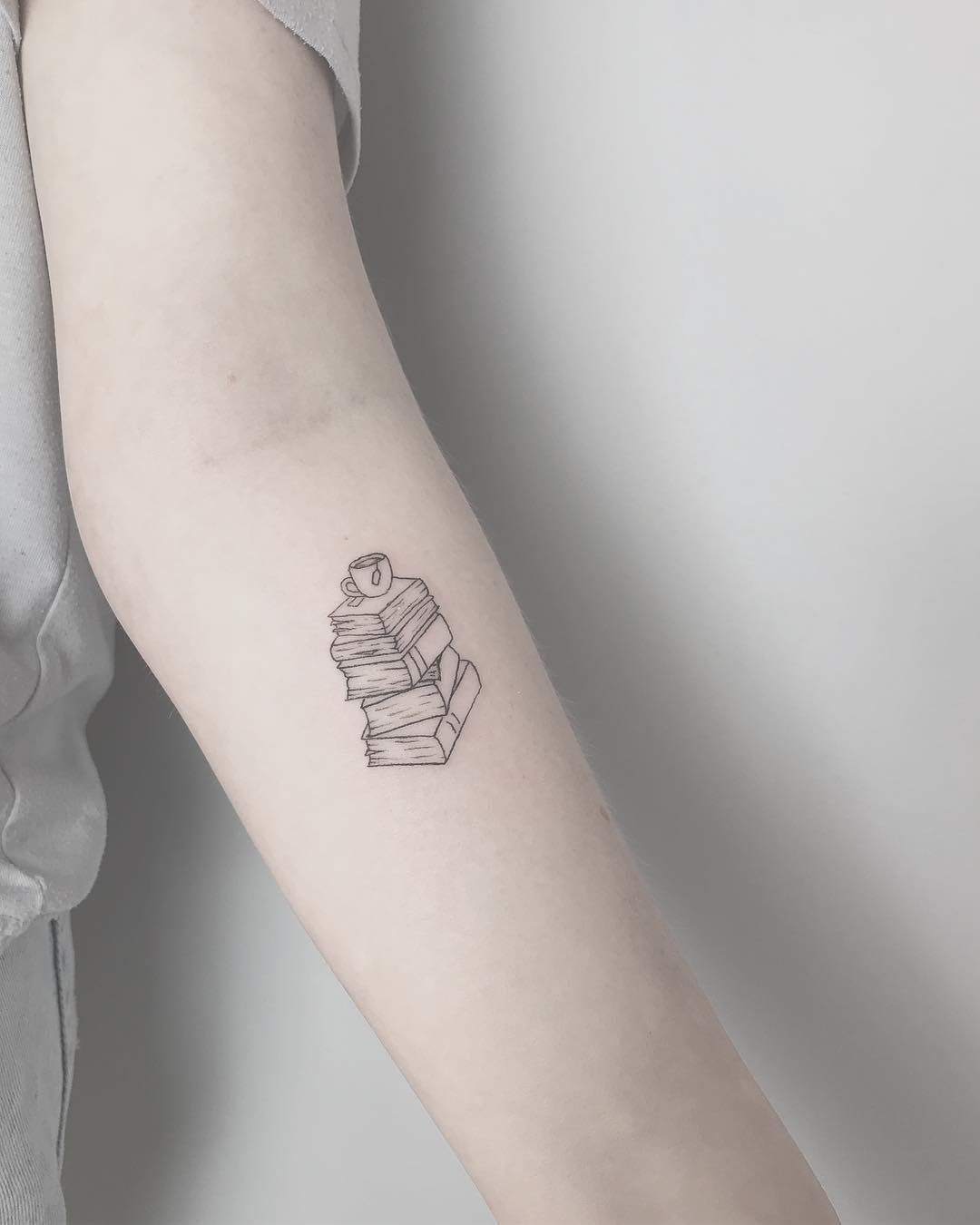 Girl with a small tattoo of books on her arm