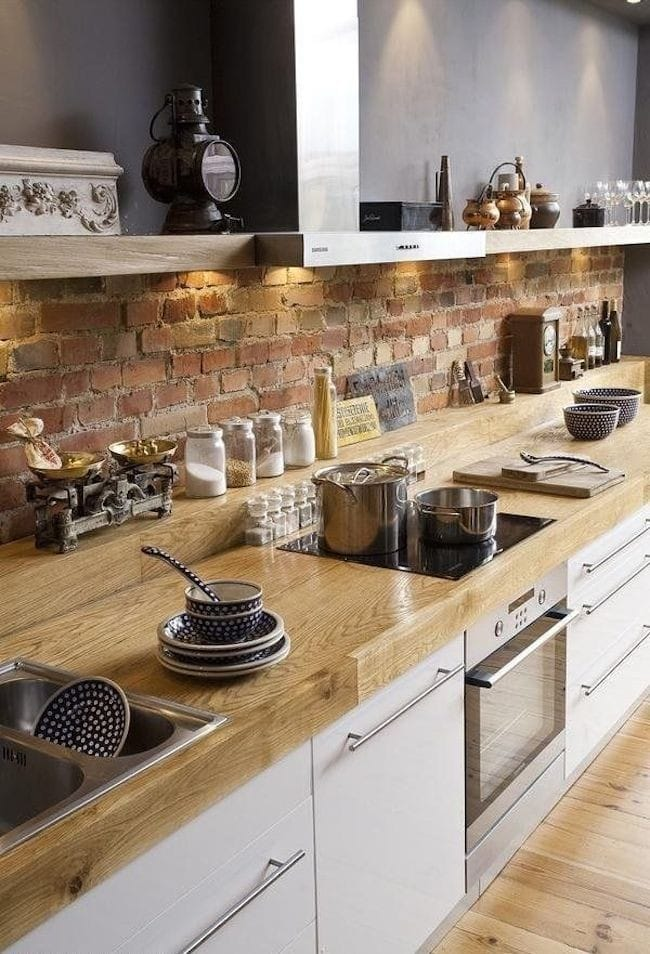 Trendy Kitchen with Exposed Brick Wall